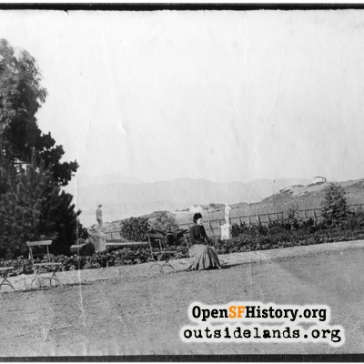 Sutro Heights. Palm Avenue. Woman seated on folding chair