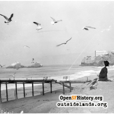 Ocean Beach. Visitor feeding seagulls near Lurline Pier, circa 1925.