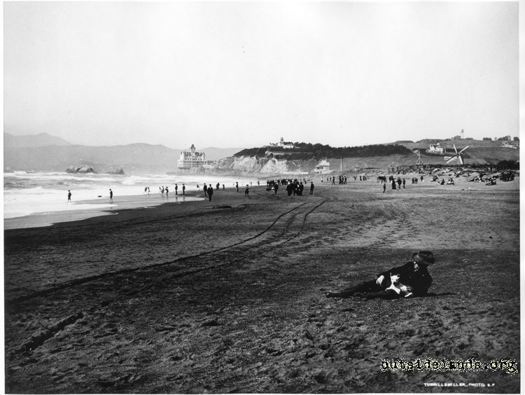 Ocean Beach visitors. Man with white dog in foreground