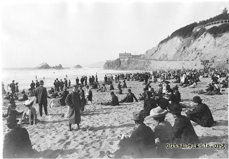 Ocean Beach. Visitors sitting on sand below Cliff House
