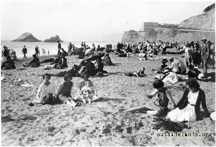 Ocean Beach. Visitors sitting on sand below Third Cliff House