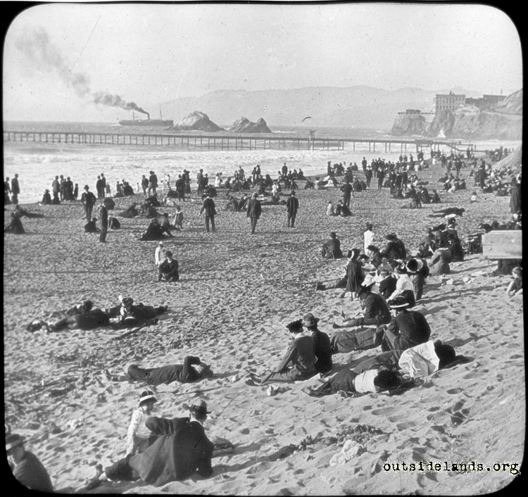 Ocean Beach. Visitors sitting on sand near Fulton St.