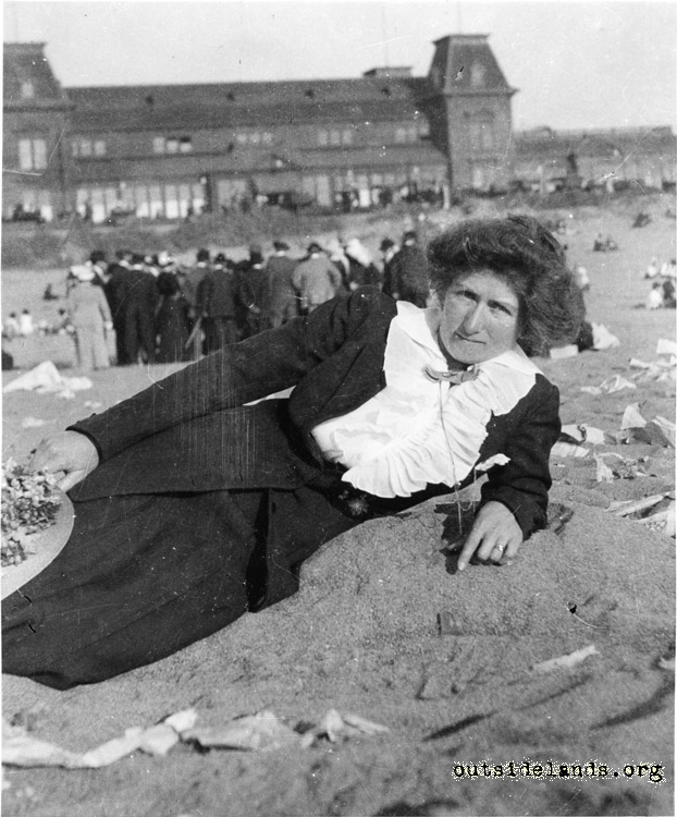 Ocean Beach. Woman in white blouse with Ocean Beach Pavilion in background.