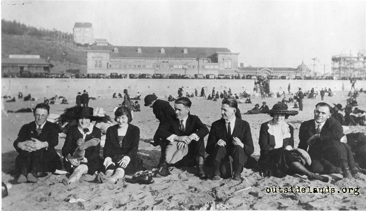 Ocean Beach. Visitors sitting on beach in front of Ocean Beach Pavilion