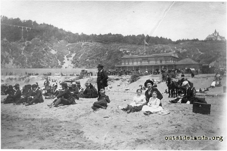 Ocean Beach. Visitors sitting on sand in front of Seal Rock Hotel