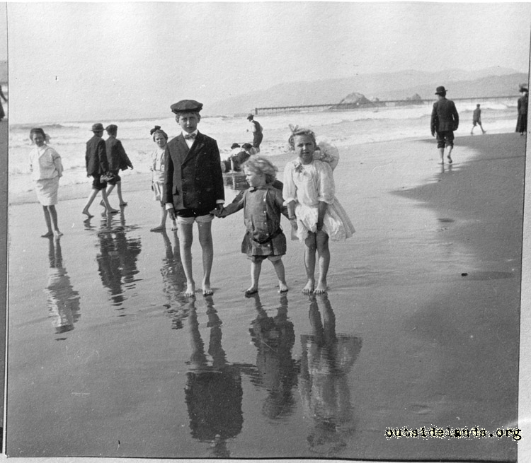 Ocean Beach visitors. Children playing on wet sand near foot of Fulton St.