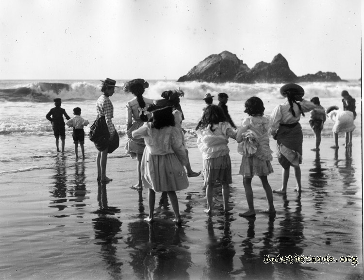 Ocean Beach. Group of kids seen from behind, playing in surf near Seal Rocks.
